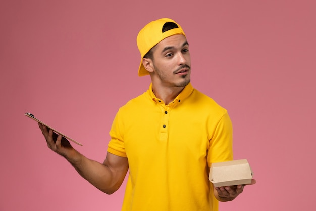 黄色の制服とケープの正面図の男性の宅配便は、淡いピンクの背景に小さな配達食品パッケージとメモ帳を保持しています。