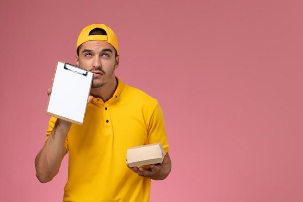 黄色のユニフォームとケープの正面図の男性の宅配便は、ピンクの背景に考えている小さな配達食品パッケージとメモ帳を保持しています。