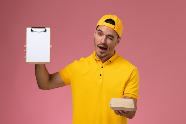 黄色のユニフォームとケープの正面図の男性の宅配便は、ピンクの背景にウィンクする小さな配達食品パッケージとメモ帳を保持しています。