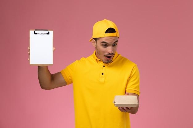 ピンクの背景に驚きの表情で小さな配達食品パッケージとメモ帳を保持している黄色の制服と岬の正面図の男性の宅配便。