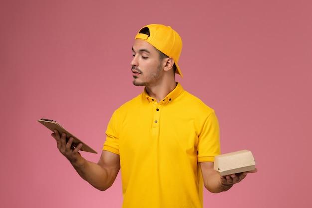 ピンクの背景に小さな配達食品パッケージのメモ帳を保持している黄色の制服と岬の正面図男性宅配便。