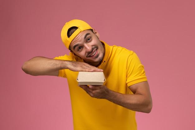 黄色のユニフォームと薄ピンクの背景に小さな配達食品パッケージを保持している岬の正面図の男性の宅配便。
