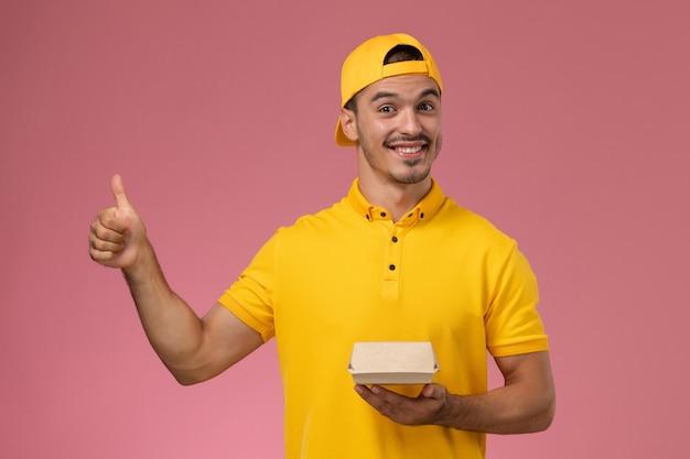 ピンクの背景に小さな配達食品パッケージを保持している黄色の制服と岬の正面図男性宅配便。