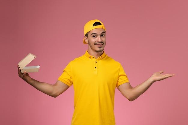 Курьер мужского пола вида спереди в желтой форме и накидке держит небольшой пакет еды доставки на розовом фоне.