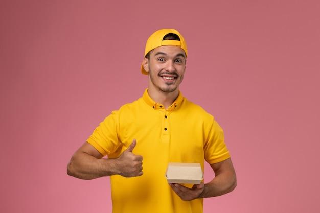 ピンクの背景に笑顔で小さな配達食品パッケージを保持している黄色の制服と岬の正面図男性宅配便。