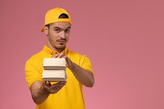 Курьер мужского пола вида спереди в желтой форме и накидке держит маленькие пакеты еды доставки на розовом фоне.
