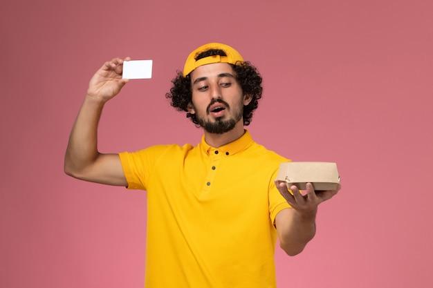 黄色のユニフォームとケープの正面図の男性の宅配便、薄ピンクの背景に彼の手にカードと小さな配達食品パッケージ。