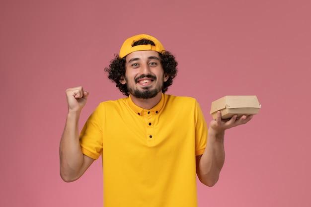 ピンクの背景で喜んで彼の手に小さな配達食品パッケージと黄色の制服とケープの正面図の男性の宅配便。