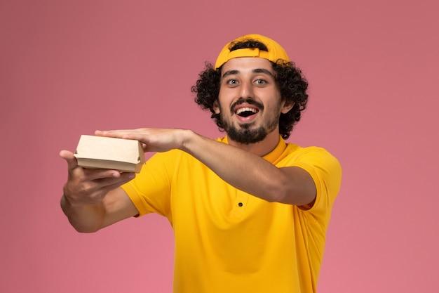 黄色のユニフォームとケープの正面図の男性の宅配便で、淡いピンクの背景に手に小さな配達用食品パッケージがあります。