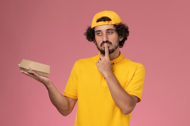 ピンクの背景に彼の手に小さな配達食品パッケージと黄色の制服とケープの正面図の男性の宅配便。