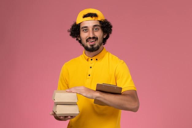 黄色のユニフォームとケープの正面図の男性の宅配便で、淡いピンクの背景に配達用の食品パッケージとメモ帳がほとんどありません。