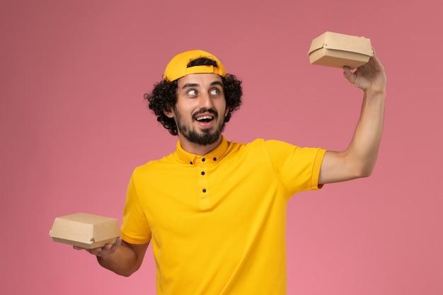 분홍색 배경에 그의 손에 작은 배달 음식 패키지와 노란색 유니폼과 케이프에서 전면보기 남성 택배.