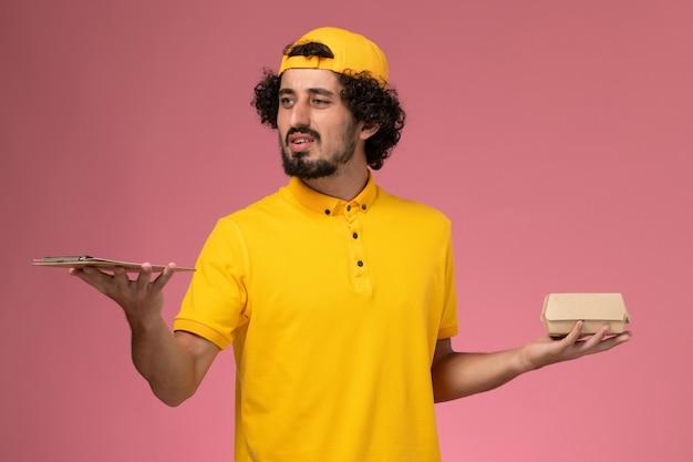 Курьер мужского пола вид спереди в желтой форме и накидке с блокнотом и небольшим пакетом еды доставки на его руках на розовом фоне.