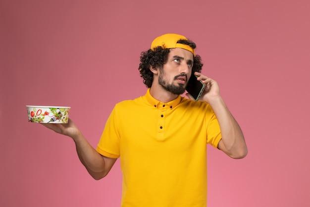 Курьер-мужчина в желтой форме с доставочной чашей и смартфоном на руках на светло-розовом фоне.