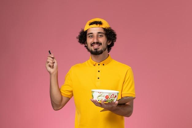 ピンクの背景にメモを書いている彼の手に丸い配達ボウルと黄色の制服ケープの正面図男性宅配便。