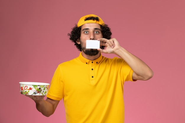 Курьер-мужчина вид спереди в желтой форменной накидке с круглой миской для доставки с белой карточкой на руках на розовом фоне.