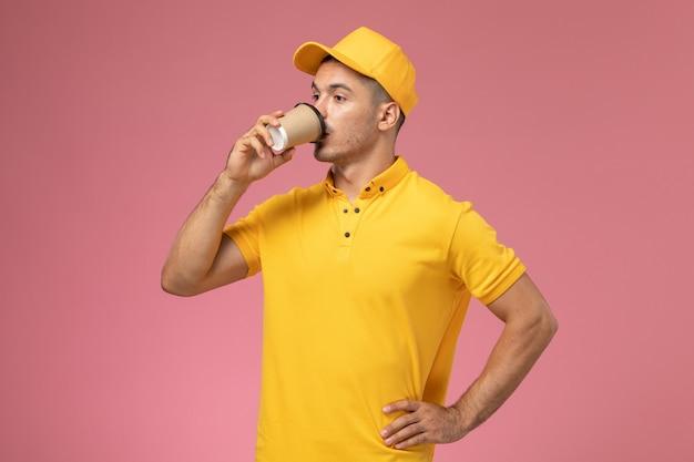 Вид спереди мужской курьер в желтой форме, пьющий кофе на розовом фоне