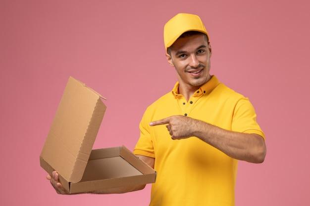 Курьер-мужчина, вид спереди в желтой форме, держит и открывает пустую коробку для доставки еды на розовом столе