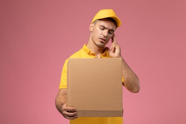 Курьер-мужчина, вид спереди в желтой форме, держит и открывает коробку для доставки еды на светло-розовом столе