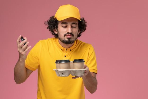ピンクの壁に香りがする茶色の配達コーヒーカップを保持している黄色の制服を着た正面図の男性宅配便