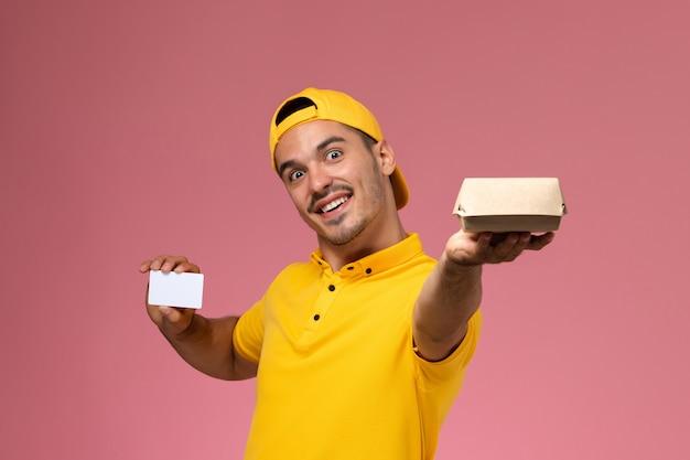 Курьер мужского пола вид спереди в желтой форме держа карточку и небольшой пакет еды на розовом фоне.