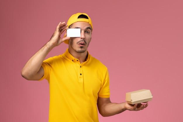 黄色の制服の保持カードとピンクの背景に小さな食品パッケージの正面図男性宅配便。
