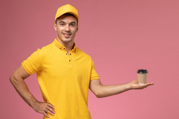 ピンクの机の上にコーヒー配達カップを保持している黄色の制服を着た正面男性宅配便