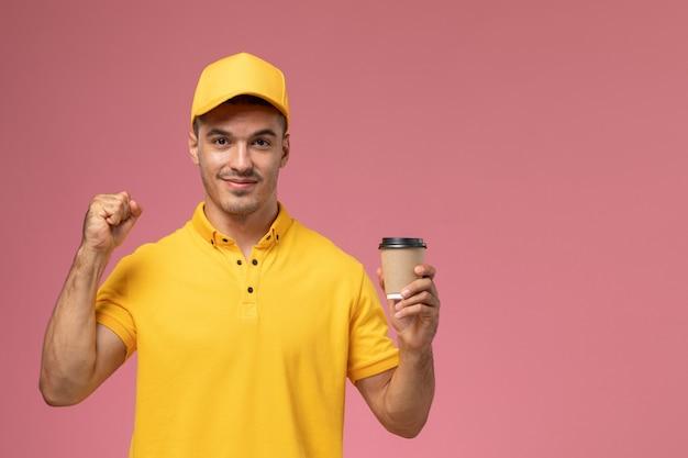 Вид спереди мужской курьер в желтой форме, держащий чашку доставки кофе с улыбкой на розовом фоне