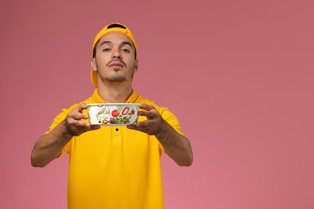淡いピンクの背景に配達ボウルを保持している黄色の制服の正面図男性宅配便。
