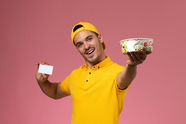 淡いピンクの背景にカードと配達ボウルを保持している黄色の制服の正面図男性宅配便。