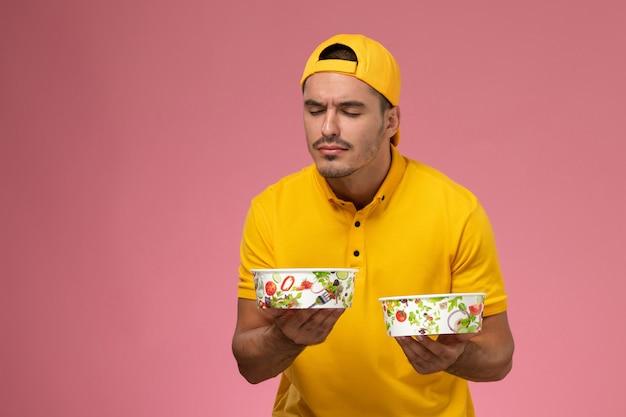 ピンクの背景に臭いがする配達ボウルを保持している黄色の制服を着た正面図の男性宅配便。