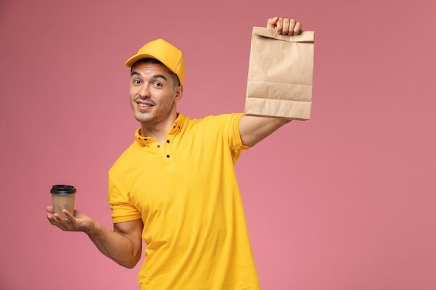 ピンクの机の上の配達のコーヒーカップと食品パッケージを保持している黄色の制服を着た正面男性宅配便