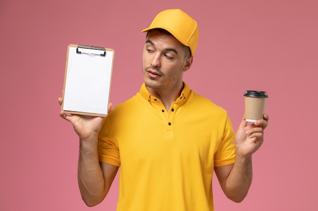 ピンクの背景に配信のコーヒーカップとメモ帳を保持している黄色の制服を着た正面男性宅配便