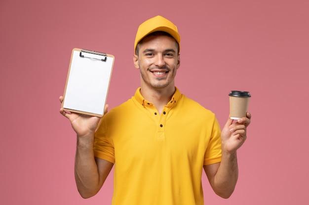 ピンクの机の上の配達のコーヒーカップとメモ帳を保持している黄色の制服を着た正面男性宅配便
