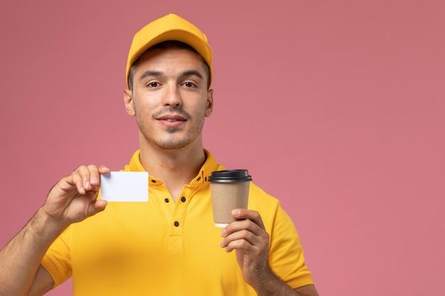 Вид спереди мужской курьер в желтой форме, держащий чашку кофе с доставкой и белую карточку на розовом фоне