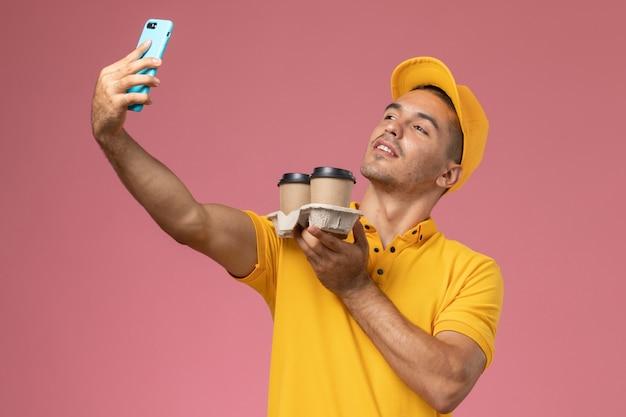 Курьер-мужчина в желтой униформе, вид спереди, держит кофейные чашки и делает селфи на розовом фоне