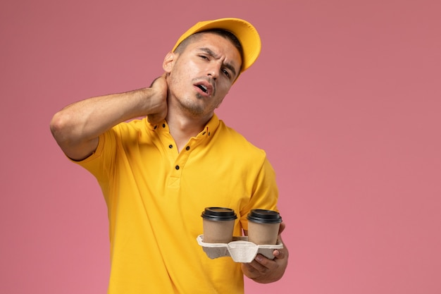 ピンクの背景に首の痛みを持っている配達のコーヒーカップを保持している黄色の制服を着た正面男性宅配便