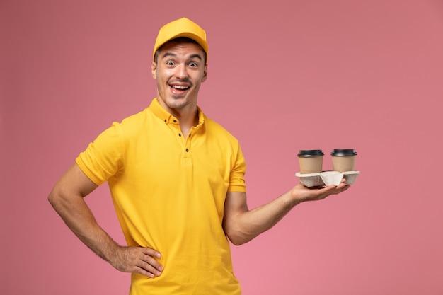 薄ピンクの背景で笑いながら配達のコーヒーカップを保持している黄色の制服を着た正面男性宅配便