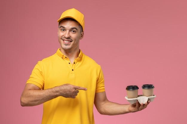 薄ピンクの机の上の配達のコーヒーカップを保持している黄色の制服を着た正面男性宅配便