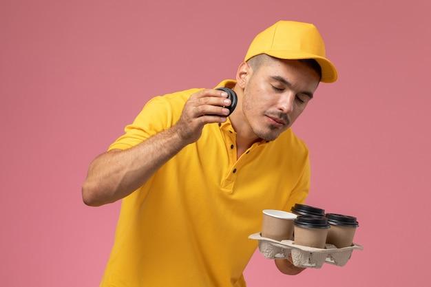 ピンクの机の上にそれらの臭いがする配信のコーヒーカップを保持している黄色の制服を着た正面男性宅配便