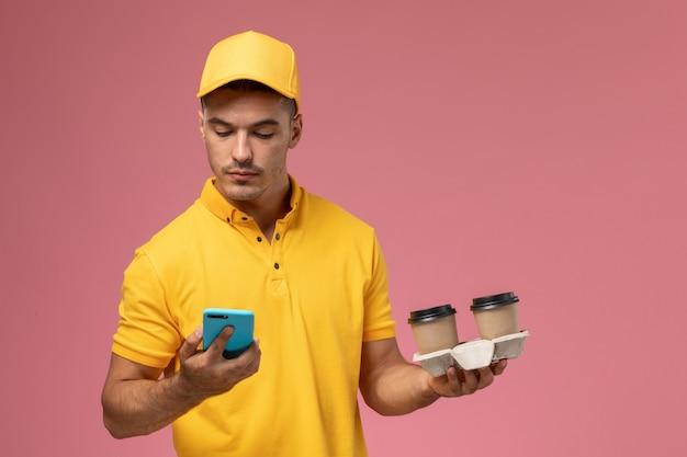 ピンクの背景に彼の電話を使用して配信のコーヒーカップを保持している黄色の制服を着た正面男性宅配便