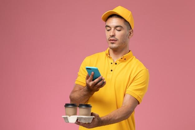 ピンクの机の上の彼の電話を使用して配信のコーヒーカップを保持している黄色の制服を着た正面男性宅配便