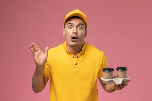 淡いピンクのデスクにショックを受けた表情で配達のコーヒーカップを保持している黄色の制服を着た正面男性宅配便