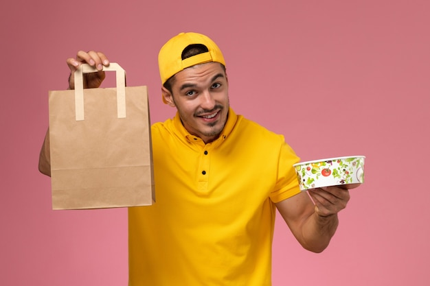 ピンクの背景に配達食品パッケージボウルを保持している黄色の制服の正面図男性宅配便。