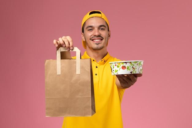 ピンクの背景に笑みを浮かべて配達食品パッケージボウルを保持している黄色の制服を着た正面図の男性宅配便。