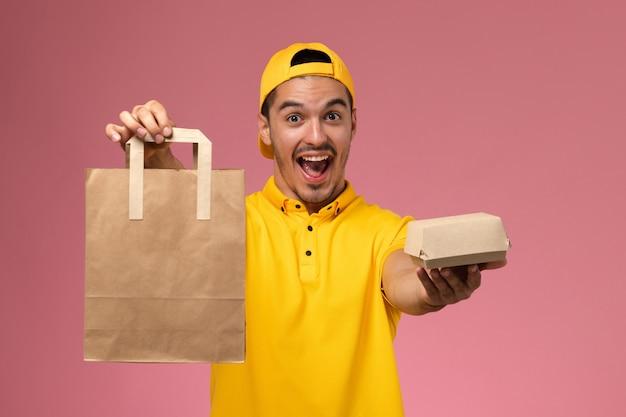 淡いピンクの机の上で応援する配達食品パッケージを保持している黄色の制服を着た正面図の男性宅配便。