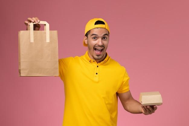 淡いピンクの背景に配達食品パッケージを保持している黄色の制服を着た正面図の男性宅配便。