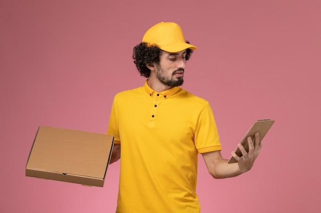 Курьер-мужчина, вид спереди в желтой форме, держит коробку для доставки еды и блокнот на розовой стене
