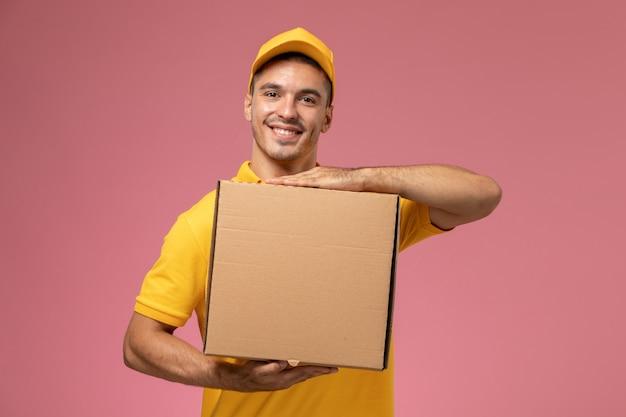 Курьер-мужчина в желтой форме, улыбаясь на розовом фоне, держит коробку для доставки еды