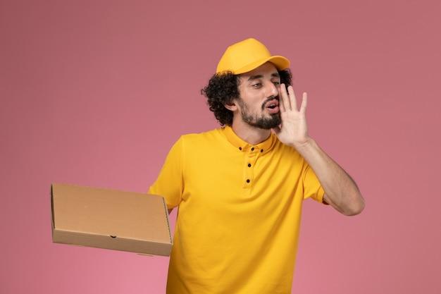Курьер-мужчина в желтой форме, держащий коробку для доставки еды, кричит на светло-розовой стене